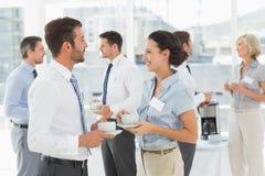 Коллеги на встреча с чашками чая во время пролома Стоковые Изображения