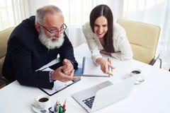 Коллеги на встрече и смотреть компьтер-книжку и дизайны Стоковое Изображение