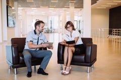 2 коллеги обсуждая идеи дела сидя на стульях в офисе Стоковые Изображения
