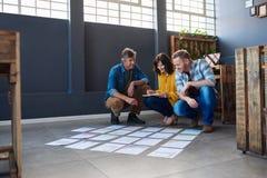3 коллеги обсуждая обработку документов клали вне на пол офиса Стоковое Изображение RF