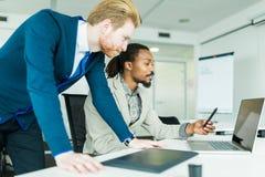 2 коллеги обсуждая ошибки проектирования графиков в славной белизне Стоковое фото RF