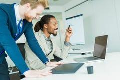 2 коллеги обсуждая ошибки проектирования графиков в славной белизне Стоковое Изображение