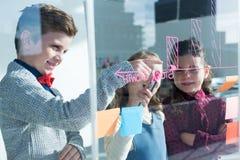 Коллеги обсуждая пока пишущ на окне увиденном через стекло на офисе Стоковая Фотография RF