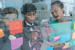 Коллеги обсуждая пока пишущ на окне увиденном через стекло Стоковое Фото