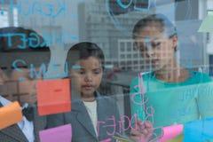 Коллеги обсуждая пока пишущ на стекле Стоковые Изображения