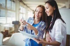 Коллеги обсуждая с цифровыми таблеткой и мобильным телефоном в творческом офисе Стоковые Фотографии RF