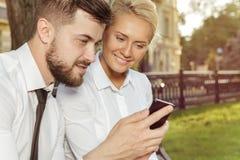 2 коллеги обсуждая что-то на мобильном телефоне Стоковая Фотография