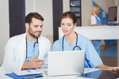 Коллеги доктора используя компьтер-книжку пока обсуждающ Стоковые Фото