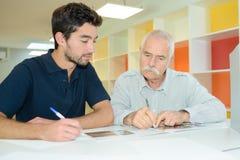 2 коллеги писать что-то на бумаге Стоковые Фотографии RF