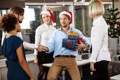 Коллеги празднуя рождественскую вечеринку в давать офиса усмехаясь представляют Стоковое Изображение RF