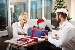 Коллеги празднуя рождественскую вечеринку в давать офиса усмехаясь представляют Стоковые Изображения RF