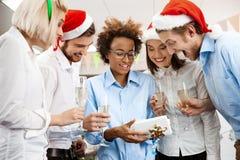 Коллеги празднуя рождественскую вечеринку в давать офиса усмехаясь представляют Стоковые Фотографии RF