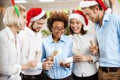 Коллеги празднуя рождественскую вечеринку в давать офиса усмехаясь представляют Стоковые Изображения