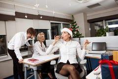 Коллеги празднуя рождественскую вечеринку в усмехаться шампанского офиса выпивая Стоковые Изображения RF