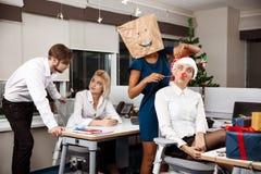 Коллеги празднуя рождественскую вечеринку в усмехаться шампанского офиса выпивая Стоковое фото RF