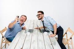 2 коллеги принимая изображению к им собственную личность сидя в офисе Стоковое Изображение RF