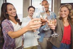 Коллеги провозглашать с шампанским в офисе Стоковое Изображение