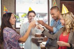 Коллеги провозглашать с шампанским на вечеринке по случаю дня рождения Стоковое Фото