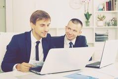 Коллеги работая вместе с компьтер-книжками Стоковое фото RF