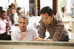 2 коллеги работая на столе с встречей в предпосылке Стоковое Изображение