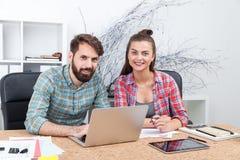 2 коллеги работая на таблице офиса Стоковая Фотография