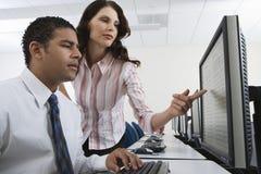 Коллеги работая совместно на компьютере Стоковые Изображения RF
