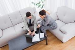 Коллеги работая совместно сидеть на софе и использование компьтер-книжки Стоковые Изображения RF