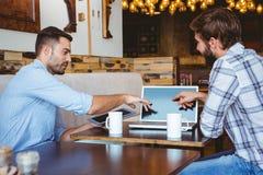 2 коллеги работая с компьтер-книжкой и tabet Стоковые Изображения RF