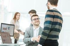 Коллеги рукопожатия около рабочего места в современном офисе Стоковое фото RF