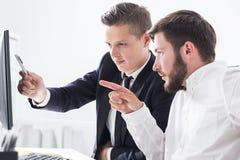 Коллеги связывая на таблице компьютера Стоковая Фотография RF