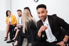 Коллеги сидя в офисе говоря друг с другом Стоковая Фотография RF