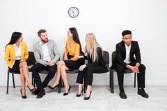 Коллеги сидя в офисе говоря друг с другом Стоковые Изображения