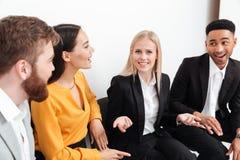 Коллеги сидя в офисе говоря друг с другом Стоковое фото RF