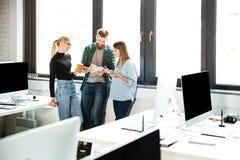 Коллеги сконцентрированные детенышами в офисе говоря друг с другом Стоковое Изображение