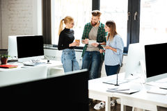 Коллеги сконцентрированные детенышами в офисе говоря друг с другом Стоковое Изображение RF