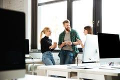 Коллеги сконцентрированные детенышами в офисе говоря друг с другом Стоковые Фото