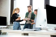 Коллеги сконцентрированные детенышами в офисе говоря друг с другом Стоковые Изображения