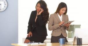 2 коллеги смешанных гонки говоря на мобильном телефоне и используя таблетку Стоковые Изображения