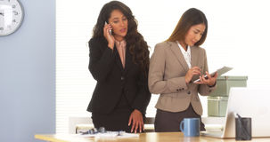 2 коллеги смешанных гонки говоря на smartphone и используя таблетку Стоковая Фотография RF