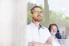 2 коллеги смотря через окно Стоковое Изображение