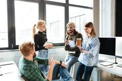 Коллеги стоя в офисе и говоря друг с другом Стоковое фото RF