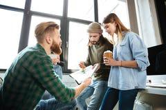 Коллеги стоя в офисе и говоря друг с другом Стоковое Изображение RF