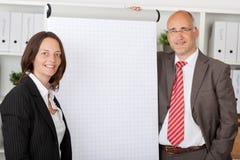2 коллеги стоя рядом с белым flipchart Стоковые Изображения RF