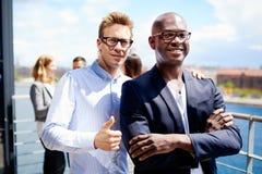 2 коллеги стоя совместно усмехающся Стоковое фото RF