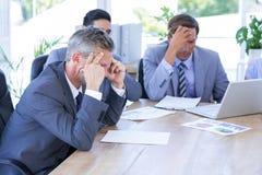 Коллеги с компьтер-книжкой и цифровой таблеткой в встрече Стоковая Фотография RF