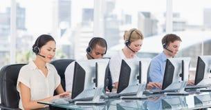 Коллеги с шлемофонами используя компьютеры на столе Стоковые Фотографии RF