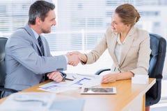 Коллеги тряся руки в деловой встрече на столе офиса Стоковые Фотографии RF