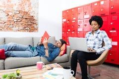 2 коллеги укомплектовывают личным составом лежать на тренере используя деятельность женщины таблетки Стоковое фото RF