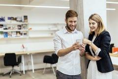 2 коллеги усмехаясь пока смотрящ телефон в офисе Стоковые Фото