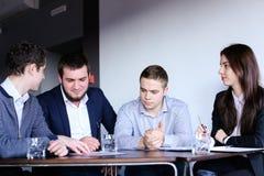 4 коллеги человека и женщины собирают для встречать на офисе  Стоковое Изображение